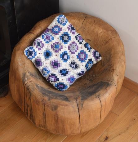 drewniane siedzisko z szydełkową poduszką